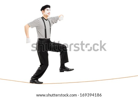 Full length portrait of a male mime artist walking on a rope, isolated on white background - stock photo