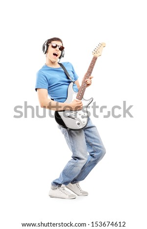 Full length portrait of a male musician with headphones playing an electric guitar, isolated on white background - stock photo