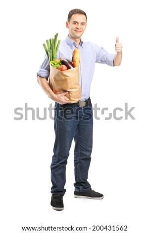Full length portrait of a man holding a bag of groceries and giving thumb up isolated on white background