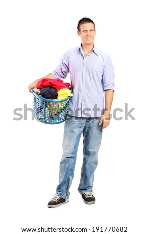 Full length portrait of a man holding a laundry basket full of clothes isolated on white background