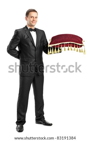 Full length portrait of a man in a black suit holding a pillow isolated on white background