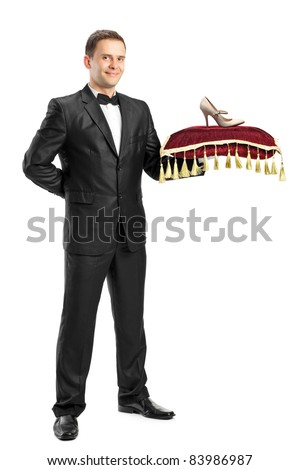 Full length portrait of a man in suit holding a pillow with a hoe on it isolated on white background