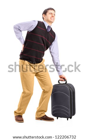 Full length portrait of a man lifting his luggage and suffering from a back pain isolated on white background - stock photo