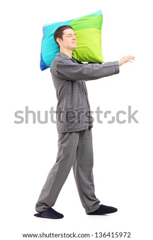 Full length portrait of a man sleepwalking and holding a pillow, isolated on white background - stock photo