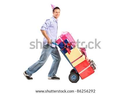 Full length portrait of a man with a party hat pushing a hand truck isolated on white background - stock photo