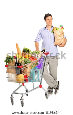Full length portrait of a man with paper bag next to a shopping cart full with groceries isolated on white background - stock photo