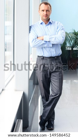 Full length portrait of a mature business man with hands folded