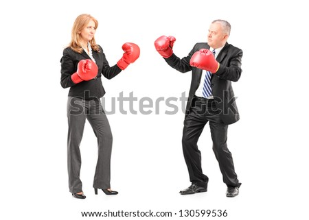 Full length portrait of a mature businessman and businesswoman with boxing gloves, isolated on white - stock photo