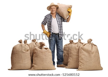 Full length portrait of a mature farmer with a burlap sack on his shoulder standing between piles of sacks isolated on white background