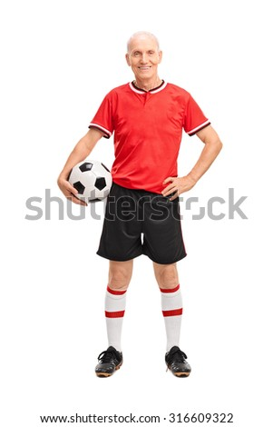 Full length portrait of a mature man in a red jersey holding a football and looking at the camera isolated on white background - stock photo