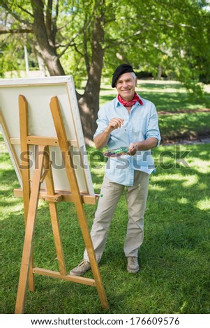 Full length portrait of a mature man painting on canvas in the park - stock photo