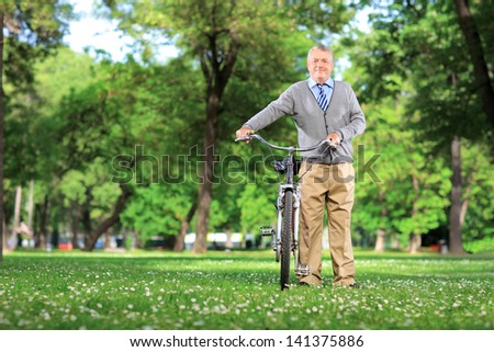 Full length portrait of a mature man with a bicycle in a park