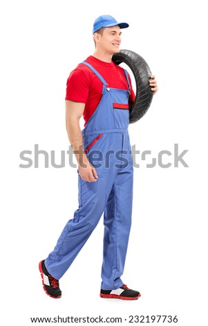 Full length portrait of a mechanic carrying a tire and walking isolated on white background - stock photo