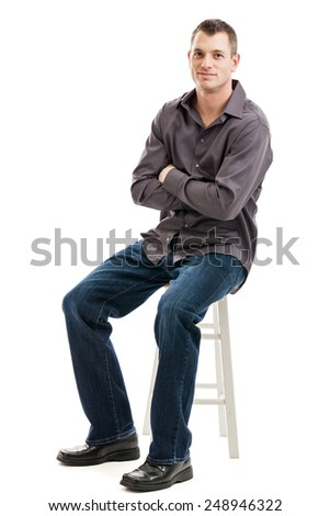 Full length portrait of a mid 30s casual business man with arms folded sitting on a stool isolated on a white background