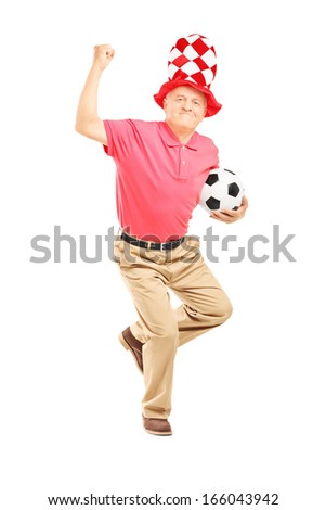 Full length portrait of a middle aged sport fan with hat holding a soccer ball and gesturing happiness isolated on white background - stock photo