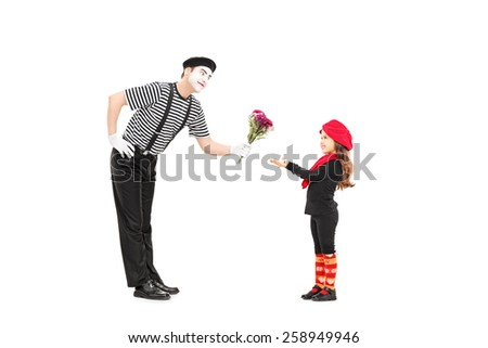 Full length portrait of a mime artist giving flowers to a little girl isolated on white background - stock photo