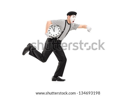 Full length portrait of a mime artist holding a clock and running late, isolated on white background