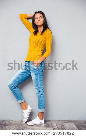 Full length portrait of a pensive fashion woman posing on gray background. Looking away - stock photo