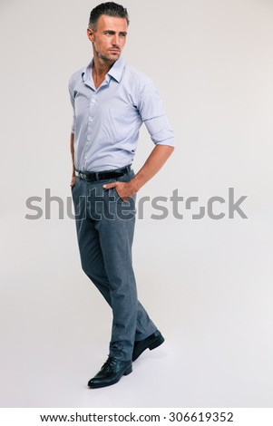 Full length portrait of a pensive man standing on gray background - stock photo