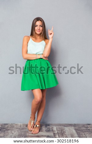 Full length portrait of a pretty girl pointing finger up and looking at camera over gray background - stock photo