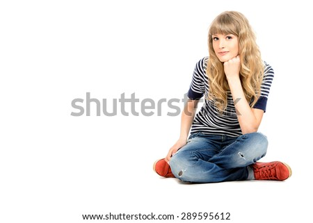 Full length portrait of a pretty teenager girl sitting on a floor. Isolated over white. - stock photo