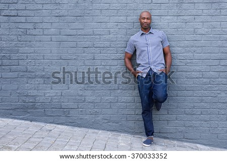 Full length portrait of a relaxed african american man leaning against wall - stock photo