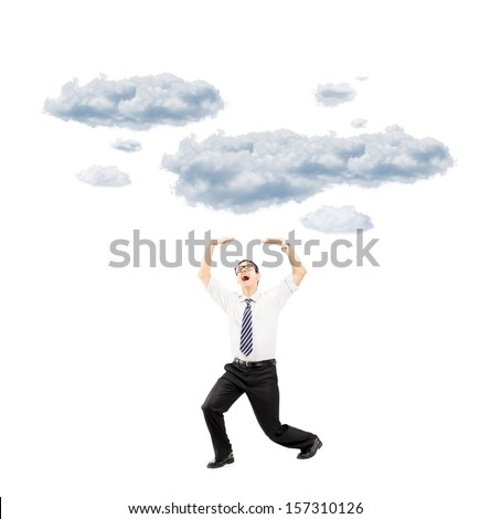 Full length portrait of a scared young man protecting from falling clouds with his hands isolated on white background