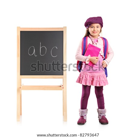 Full length portrait of a school kid posing next to a school board isolated on white background