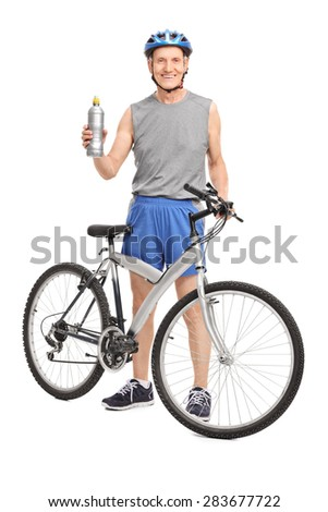 Full length portrait of a senior cyclist holding a water bottle and posing behind his bicycle isolated on white background