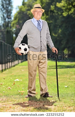 Full length portrait of a senior gentleman holding a football in park