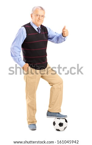 Full length portrait of a senior gentleman with ball giving thumb up isolated on white background - stock photo