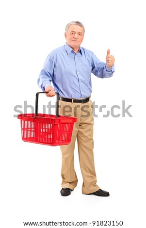 Full length portrait of a senior man holding an empty shopping basket and giving thumb up isolated on whte background - stock photo