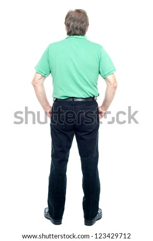 Full length portrait of a senior man looking at the wall. Back pose - stock photo