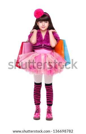Full length portrait of a serious girl holding shopping paper bags on white background