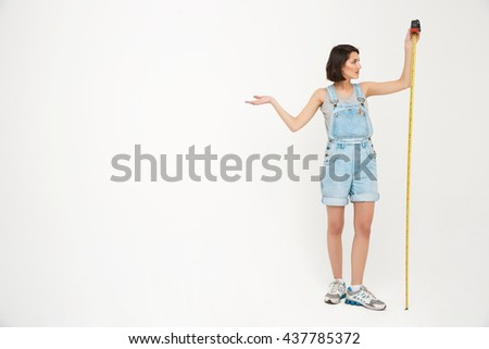 Full length portrait of a seriously pretty girl, in gray shirt and denim overall, holding measure tape, isolated on white background - stock photo