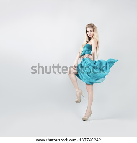 Full Length Portrait of a Sexy Blonde Woman in Turquoise Fashion Dress - stock photo