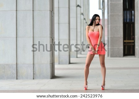 Full length portrait of a sexy brunette woman in little pink fashion dress - stock photo