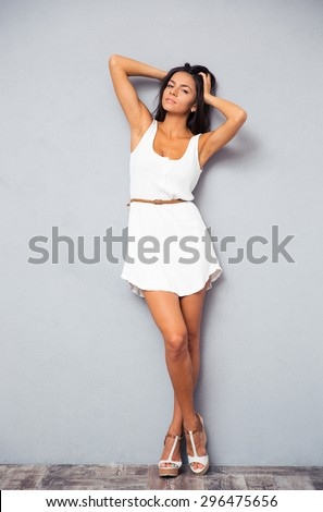 Full length portrait of a sexy cute female model in fashion white dress posing at studio and looking at camera - stock photo