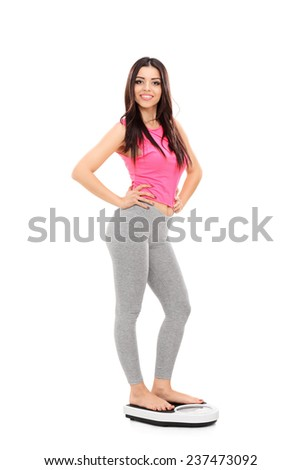 Full length portrait of a sexy girl standing on a weight scale isolated on white background - stock photo