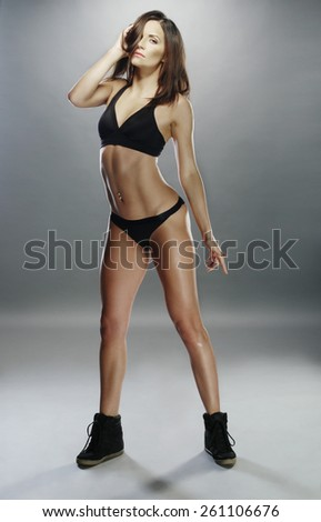 Full Length Portrait of a Sexy Gorgeous Woman Posing in Black Sporty Underwear and Shoes and Looking at the Camera on a Gray Background. - stock photo