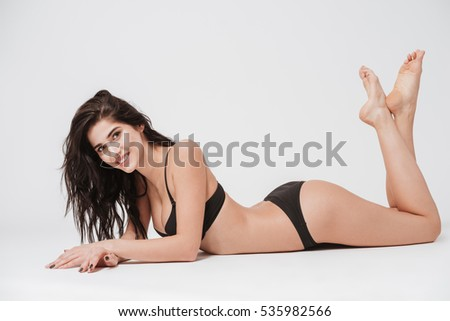 Full length portrait of a sexy yuong woman in lingerie laying on the floor and looking at camera isolated on the white background
