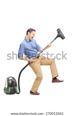 Full length portrait of a silly young man imagining that he�¢??s playing guitar on a vacuum cleaner isolated on white background - stock photo