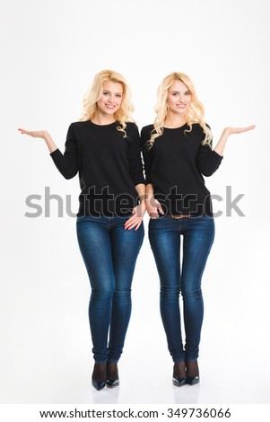 Full length portrait of a sisters twins holding copyspace on the palms isolated on a white background - stock photo