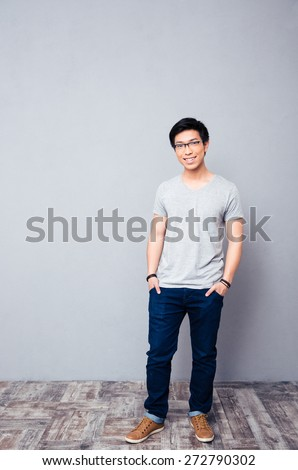 Full length portrait of a smiling asian man standing in studio and looking at camera - stock photo