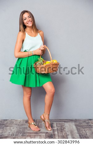 Full length portrait of a smiling attractive woman holding basket with fruits over gray background - stock photo