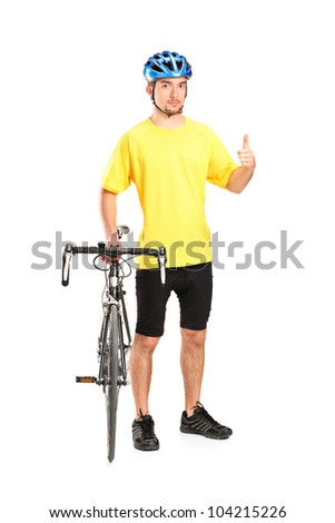 Full length portrait of a smiling bicyclist posing next to a bicycle and giving thumb up isolated on white background