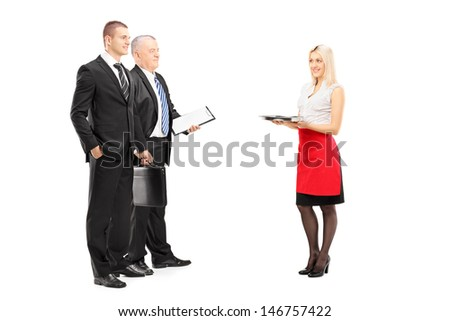 Full length portrait of a smiling blond waitress with tray serving two businessmen isolated on white background - stock photo