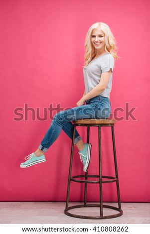 Full length portrait of a smiling blonde woman sitting on the chair over pink background and looking at camera - stock photo