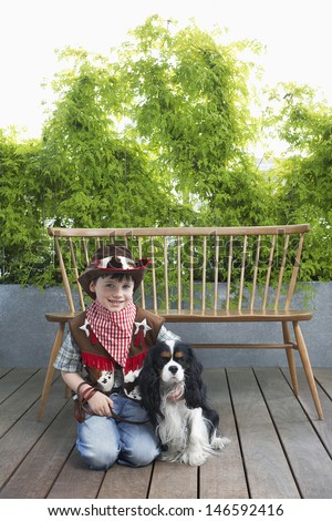 Full length portrait of a smiling boy in cowboy costume kneeling with dog on deck - stock photo
