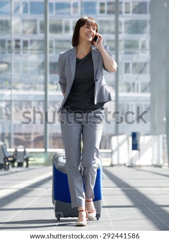 Full length portrait of a smiling business woman talking on mobile phone at airport - stock photo